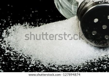 Pile of spilled salt and saltshaker black isolated