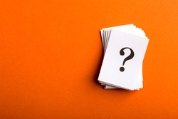 Pile of stacked question marks printed on sheets of white paper or signs arranged to the side on a orange background with copy space in a conceptual image.