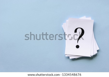 Pile of stacked question marks printed on sheets of white paper or signs arranged to the side on a blue background with copy space in a conceptual image