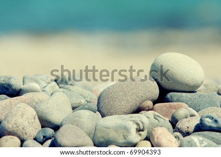 pile of stones isolated on a blur sea background with sunlight - stock photo