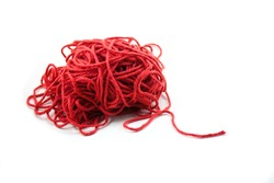 Pile of tangled red yarn with a single end leading out. Isolated on white