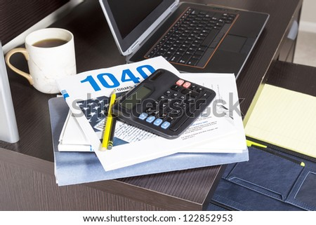 Pile of tax returns with computer, cup of coffee and calculator on desk