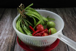 Pile of traditional ingredients in Thai local cuisine, bunch of acacia, fresh red chilly, organic cherry tomato and lime in the plastic basket. Famous tropical vegetable concept.