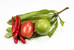 Pile of traditional ingredients in Thai local cuisine, bunch of acacia, fresh red chilly, organic cherry tomato and lime isolated on the white background. Famous tropical vegetable concept.