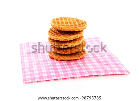 Pile of typical Dutch stroopwafels ( with syrup) on napkin over white background