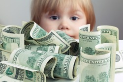 Pile of United States dollar hundred USD banknotes on white table and blurred baby looking on it on a background. Retro tonal correction photo filter effect, selective focus on money
