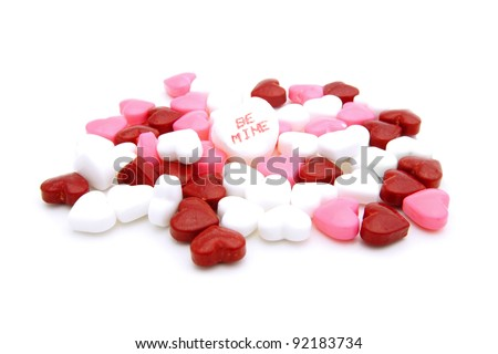 "Pile of Valentines Day heart-shaped candies with ""Be Mine"" conversation heart"