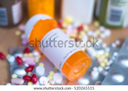 Pile of various expired prescription medicines and bottle focused on expired date. Antibiotic , paracetamol, vitamins drugs. International Day against Drug Abuse and Illicit Trafficking