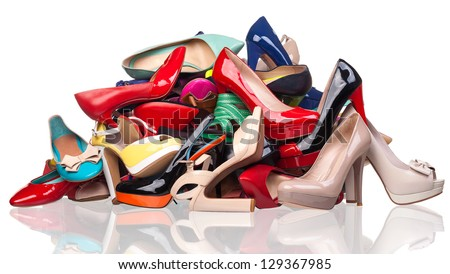 Pile of various female shoes over white