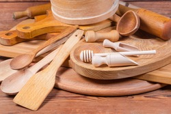 Pile of various kitchen utensils made with different natural wood type on an old rustic table