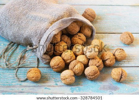 Pile of walnuts in shellin a bag on a wooden background . Linen sack with walnuts in the background.