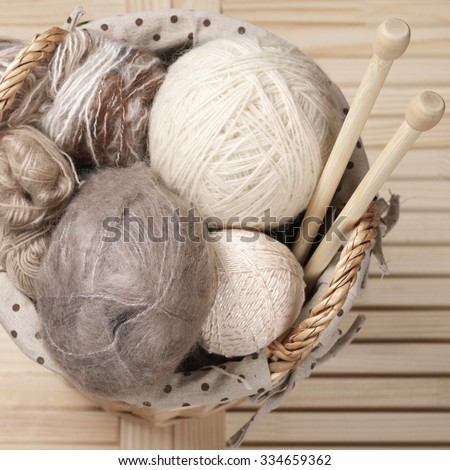 Pile of warm woolen yarn and wood needles in rustic wicker basket on wooden table. Top view point.