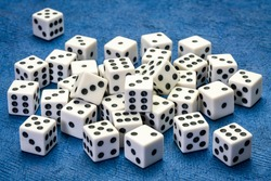 pile of white cubic dice with black pips (dots) against blue handmade paper, game, gamble, chance and risk concept