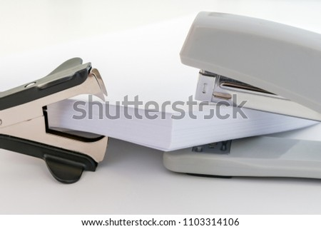 pile of white office paper between a black stapler remover and a gray stapler over a white background, concept abstract background
