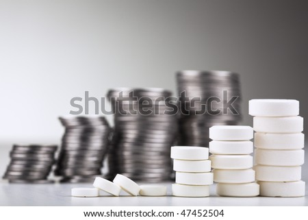 Pile of white pills (in the form of a staircase) against pile of coins