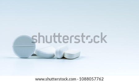 Pile of white round and oblong shape tablet pills isolated on white background. Pharmaceutical industry. Pharmacy or drugstore sign and symbol. Global healthcare concept. Health and pharmacology.