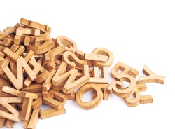 Pile of wooden block letters isolated over the white background as a typography background composition