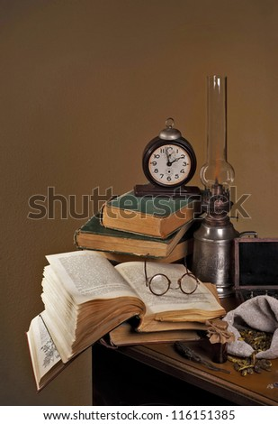 Pile old books and ancient lamp on dark and light background