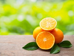 Pile orange fruit and orange slice with green leaf on wooden table of natural background with copy space
