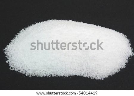 Pile Pickling Salt over black. Picture of Pile Pickling Salt, which is fine grain not iodine sea salt  on black background used for Pickling of Food.