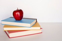 Pile stack of books with red apple on top sitting on a desk top, back to school concept, education teacher concept, horizontal shot copy text space, white background