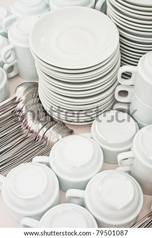 pile white tea tableware and spoons - stock photo