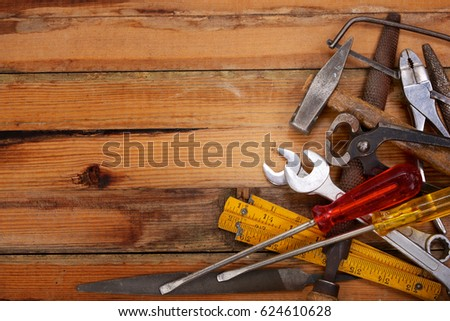 Piled hand tools on a wooden workbench #624610628