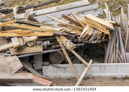 Piled in a pile of debris, pieces of boards, plywood and concrete blocks. Lumber, garbage, firewood