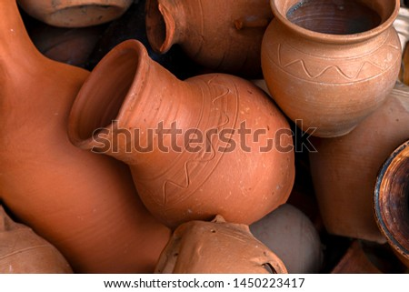 Piled in a pile of forgotten old pottery, jugs, pots.