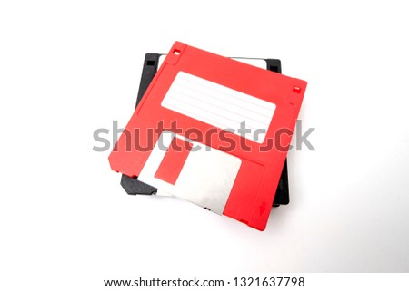 Piled obsoleted black diskettes with red diskette on the top