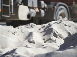 Piled up Fine White Sand Construction Material with Truck in Background