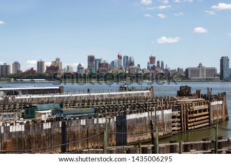 Piles in the port of New York, on the background are the skyscrapers of Manhattan. Skyscrapers are seen in the bay bay. #1435006295
