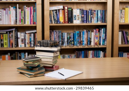 Piles of books, a notepad and a pen