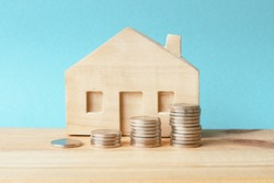 Piles of coins and a wooden  house on a blue background. Concept - real estate investment, family budget or money to pay rent or purchase a home.