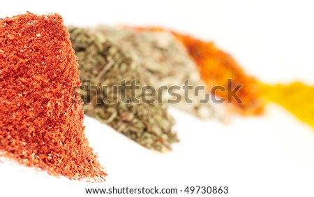 Piles of different spices, focus is on the first (paprika)