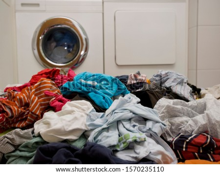 Piles of dirty laundry near washing machine