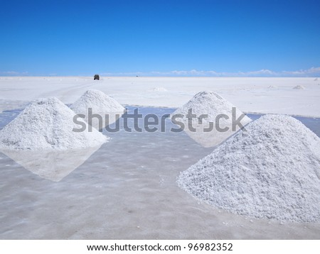 Piles of drying salt and reflection in the water at the Salar de Uyuni (salt flats) in Bolivia.
