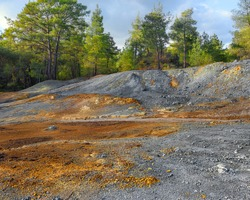 Piles of multicolored rocks in a forest, tailings from pyrite mining at abandoned open pit copper mine