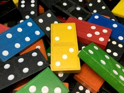 Piles of multicolour wooden dominoes with white dots for math