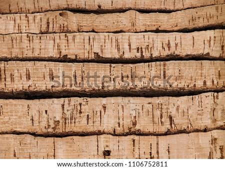 Piles of natural cork barks close up - planks of the cork tree for your textured background. Raw cork boards for making classic bottles stoppers for wine and champagne.