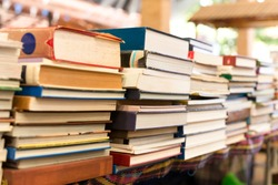 Piles of old books on a table in blur background