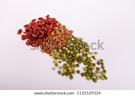 Piles of raw pinto red kidney and lentil beans on solid white background