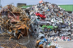 Piles of scrap metal, including cars waiting to be recycled at a processing plant.