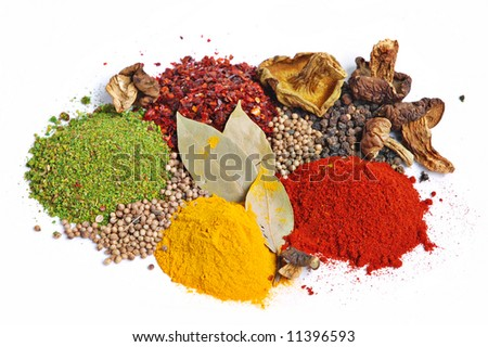 Piles of spices: parsley, red paprika, whole black pepper, white coriander, curcuma, laurel leaves and dry porcine mushrooms.