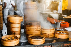 Piles of stacking bamboo steamers are steaming for dim sum in front of the restaurant with blur chefs in background in Taipei, Taiwan. Focus on front bamboo steamers.