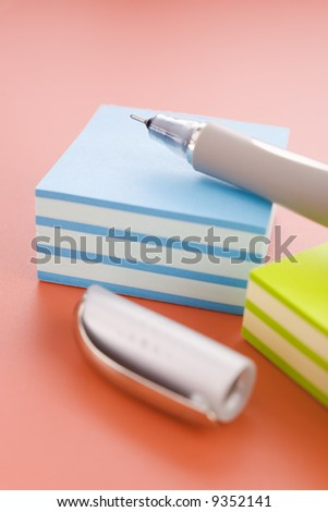 Piles of sticky notes and pen over a red table
