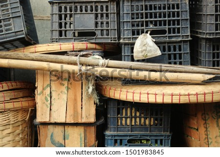 piles of timber and plastic food transport crates piled high by the side of the road at a market in Southeast Asia #1501983845
