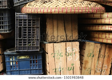 piles of timber and plastic food transport crates piled high by the side of the road at a market in Southeast Asia