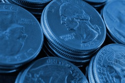 Piles of US American coins of 25 cents quarters close-up. Dark blue tinted background for news about USA money, economy, investment, dollar, state budget and Fed. Backdrop or wallpaper. Macro