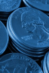 Piles of US American coins of 25 cents quarters close-up. Dark blue vertical background for news about USA money, economy, investment, dollar, state budget and Fed. Backdrop or wallpaper. Macro